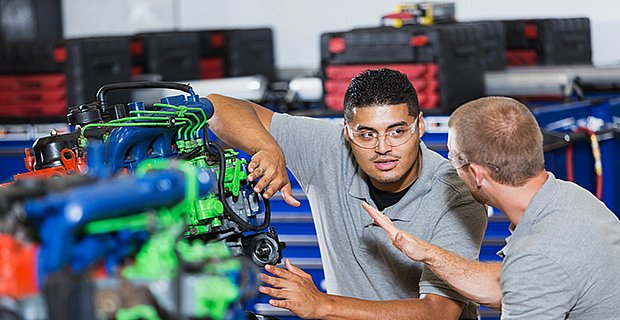 Two multi-ethnic young men in vocational school, taking a class on reparing diesel engines.  They are working on an engine that has had parts painted different colors for training purposes.  They are wearing safety glasses.