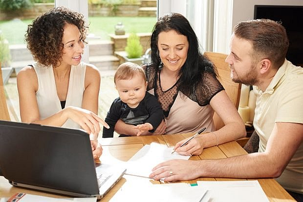 a young husband and wife with their baby sit and chat to a woman in their dining room . They are all referring to a laptop in front of them and various paperwork is dotted about the table.
