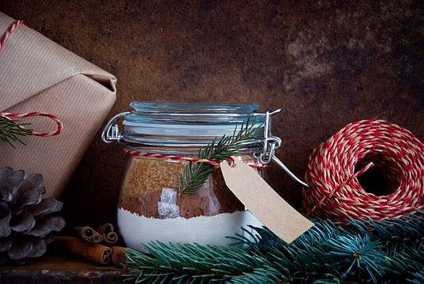 Homemade Christmas Cake Mix in a Jar decorated with pine cones and spruce branches on a dark wooden background