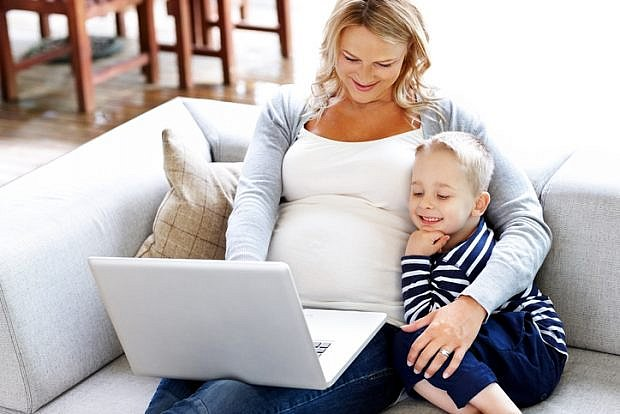 Expectant mother sitting on couch with her son using laptop computer at home
