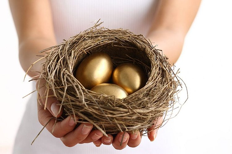 woman holding nest with golden egg to represent superannuation guarantee contributions