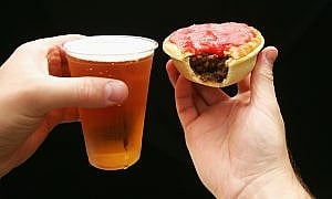 A beer in a plastic cup and a meat pie covered in sauce with a bite out of it. Standard meal at the footy